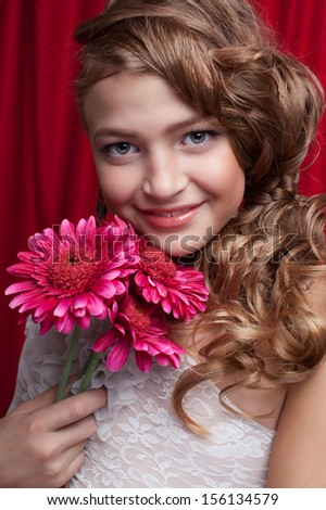 pretty smiling model girl with gerbera flower. Hairstyle and makeup. long white bride dress