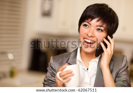 Pretty Smiling Multiethnic Woman with Coffee and Talking on a Cell Phone in Her Kitchen.
