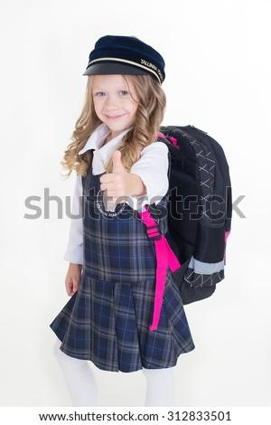 Pretty smiling schoolgirl in uniform thumbs up - stock photo