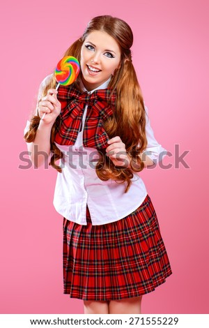 Pretty smiling teen girl in school plaid skirt and white blouse posing with lollipop over pink background. Anime style.  - stock photo