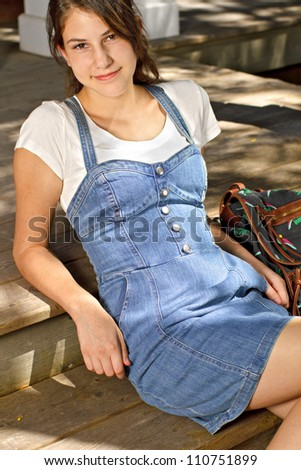 Pretty smiling teenage girl in fashionable back to school clothes sitting on steps with backpack beside her. Vertical, copy space