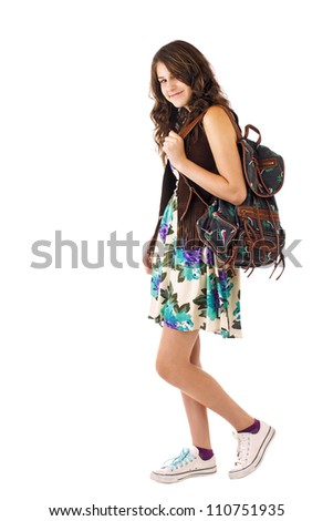 Pretty smiling teenage girl in flowered dress and fringed vest carries a backpack while strolling. Vertical, isolated on white, copy space. - stock photo