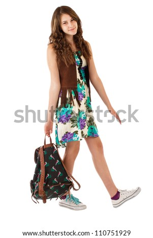 Pretty smiling teenage girl in flowered dress and fringed vest walks and carries a backpack. Vertical, isolated on white, copy space.