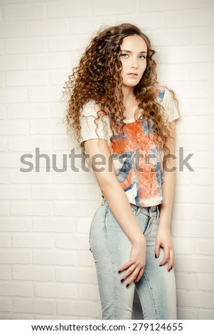 Pretty smiling teenage girl posing by the brick wall. Casual jeans style. - stock photo