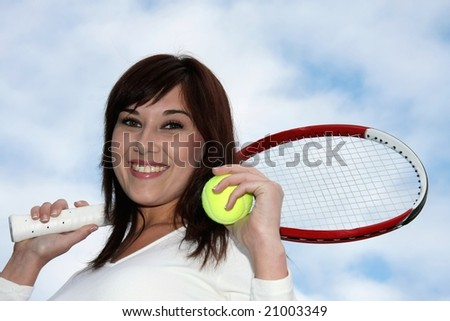 Pretty smiling tennis player with racket and ball