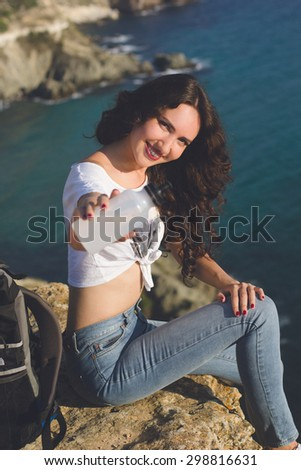 Pretty smiling traveler girl backpacker is drinking water on rock peak over sea view with backpack, summer vacations, split tonning image - stock photo