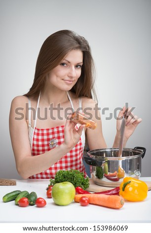 Pretty smiling woman in an apron seasoning soup with paprika - stock photo