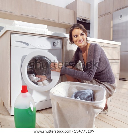 pretty smiling woman in the laundry room - stock photo