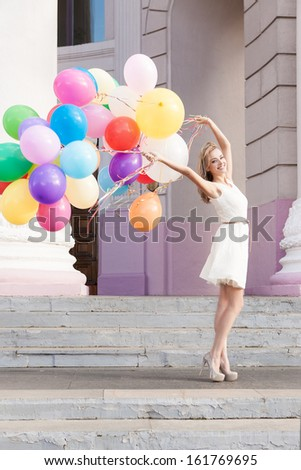 pretty smiling woman in white summer dress holds a bunch of multicolored balloons in front of old building with columns