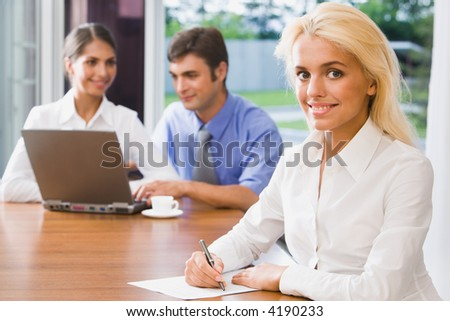 Pretty smiling woman on a background of her the coworkers in the office