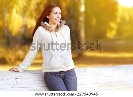 Pretty smiling woman outdoors enjoying warm sunny autumn weather - stock photo