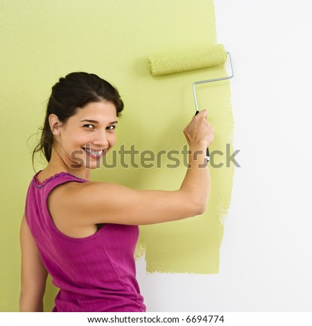 Pretty smiling woman painting interior wall of home with paint roller.