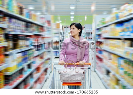 pretty smiling woman pushing shopping cart looking at goods in supermarket - stock photo