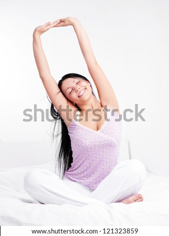 pretty smiling woman sitting on the bed at home waking up and stretching - stock photo