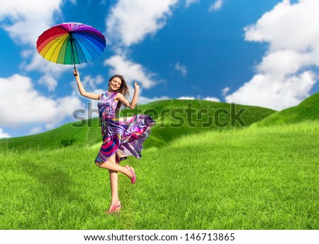 Pretty smiling woman with colorful umbrella posing for photo among the green hills