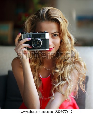 Pretty smiling woman with retro film camera, take a picture - stock photo