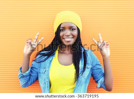 Pretty smiling young african woman having fun over orange background - stock photo