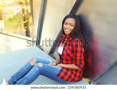 Pretty smiling young african woman wearing a red checkered shirt sitting in city - stock photo