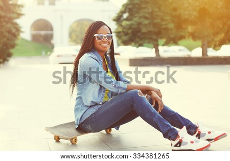 Pretty smiling young african woman with skateboard in city - stock photo