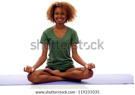 Pretty smiling young black woman doing yoga exercise on mat isolated over white - stock photo