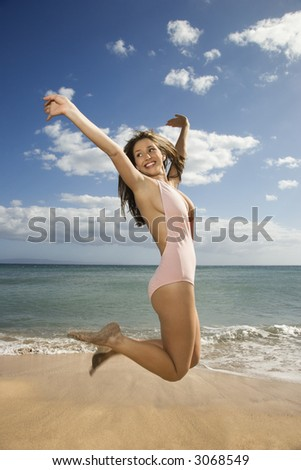 Pretty smiling young Caucasian woman in swimsuit jumping into air at beach in Maui Hawaii. - stock photo