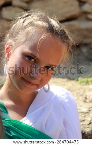 Pretty smiling young girl in a vintage tunic as a Greek goddess on a background of the archaeological site of the ancient city in the village Geroevskoe, Republic of Crimea - stock photo