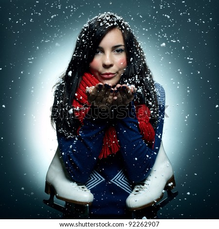Pretty smiling young girl with the skates. Winter portrait. Snowfall - stock photo