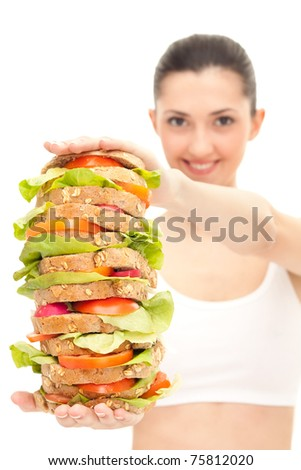 pretty,  smiling young woman giving us a huge sandwich, isolated on white - stock photo