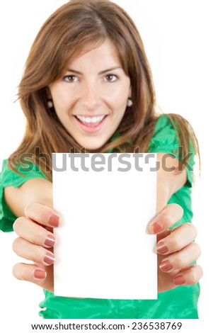 pretty smiling young woman or girl in green shirt holding in both hands business card or note against white background. Copy space for text and marketing ideas and slogans. Focus on blank white card - stock photo