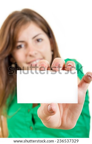 pretty smiling young woman or girl in green shirt holding in hand business card against white background. Copy space for text and marketing ideas and slogans. Focus on blank white card - stock photo