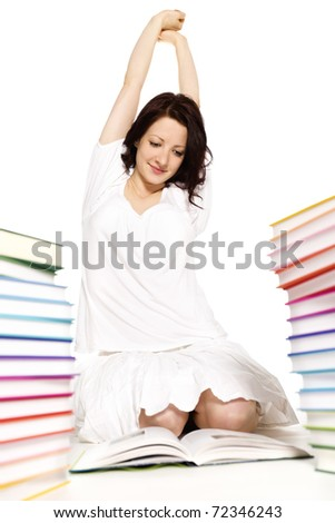 Pretty smiling young woman sitting on floor between two stacks of colorful books reading and stretching herself, isolated on white background. - stock photo