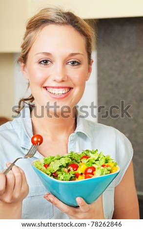 Pretty smiling young woman standing in the kitchen and holding a bowl with salad