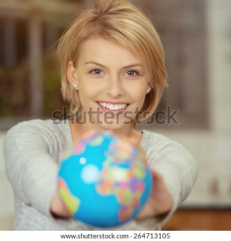Pretty Smiling Young Woman with Blond Hair Showing Small World Globe on Hand While Looking at the Camera. - stock photo