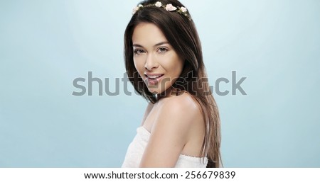 Pretty Smiling Young Woman with Small Flower Headband Wrapped in a Bath Towel While Looking at the Camera. Isolated on a Sky Blue Background - stock photo