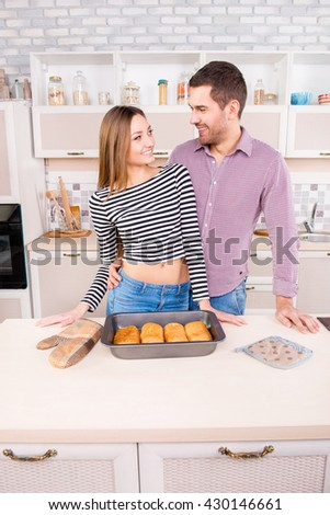 Pretty smilling couple in love with baked pies in the kitchen - stock photo