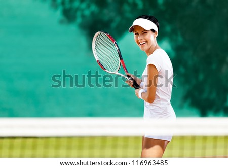 Pretty sportswoman with racquet at the tennis court. Healthy lifestyle - stock photo