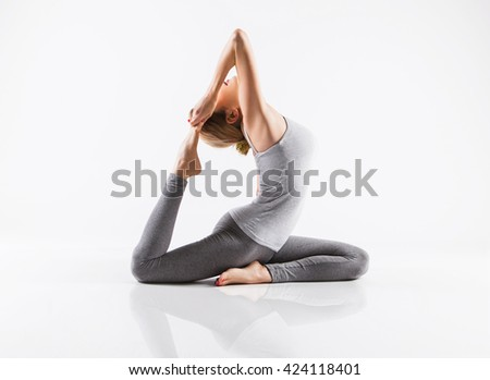 Pretty sporty blonde in doing yoga on white background - stock photo