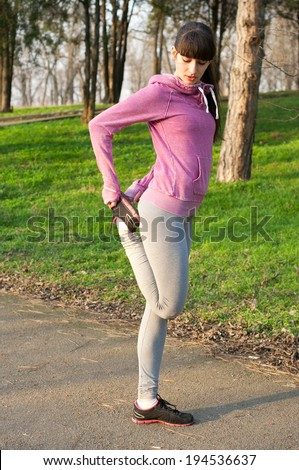pretty sporty brunette woman runner stretching stock photo
