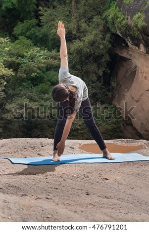 Pretty sporty fit woman prepare to practices yoga asana (pose) at the stone park.Health concept .selective focus.