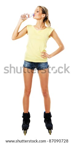 Pretty sporty girl in roller skates drinking mineral water