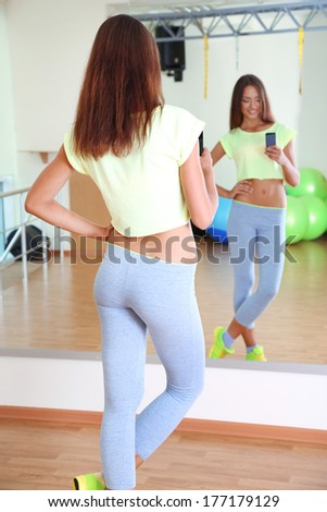 Pretty sporty girl photographing herself in mirror at phone in fitness room