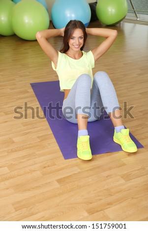 Pretty sporty girl swing press in fitness room - stock photo