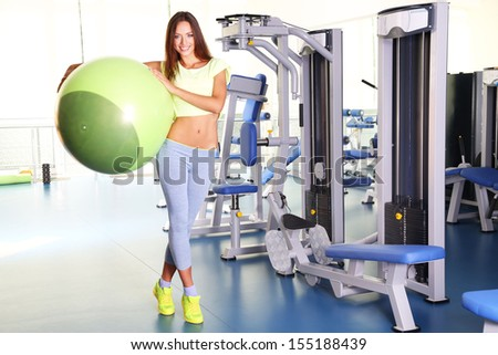 Pretty sporty girl with fit-ball in gum - stock photo