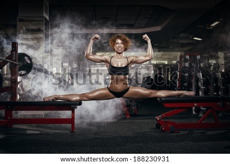 Pretty sporty strong slim and fit young woman sitting, doing split and stretching exercises, sitting on a full split. In the gym