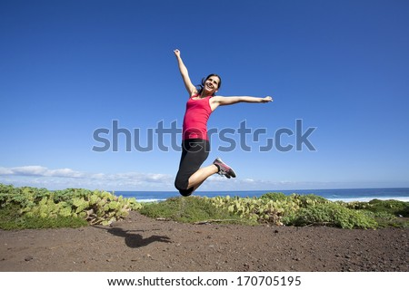 pretty sporty young woman jumping of joy outdoor - stock photo