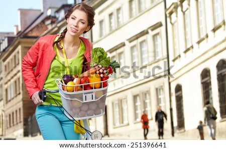 Pretty spring woman with bicycle and groceries in old town street. - stock photo