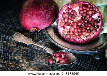 Pretty Still Life Closeup of an Open Red Pomegranate in dark setting on Wood Table for eating, cooking, baking, garnish, smoothies, alcoholic beverage, cocktails and wine.  Horizontal looking down - stock photo