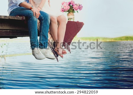 Pretty strong young loving couple sitting on the bridge over the river, next to a bouquet of peonies, lifestyle, concept, love, tenderness - stock photo