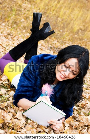 pretty student doing homework in the park - stock photo