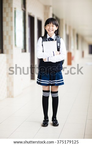 pretty  student girl holding books in front of  classroom - stock photo